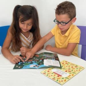Enfants qui lisent un carnet d'activités