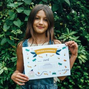 Enfant avec son diplôme sur les insectes