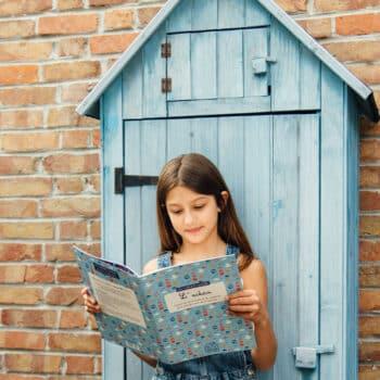Fille lisant son carnet d'activités sur l'océan