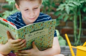 Garçon lisant le carnet sur la potager